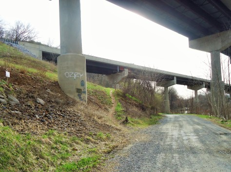 Trail goes right under I-81 then veers uphill to the left.
